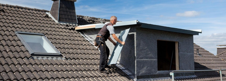 Man is een dakkapel op een huis aan het plaatsen